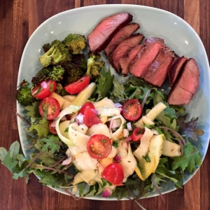 sirloin steak served with summer squash salad and broccoli